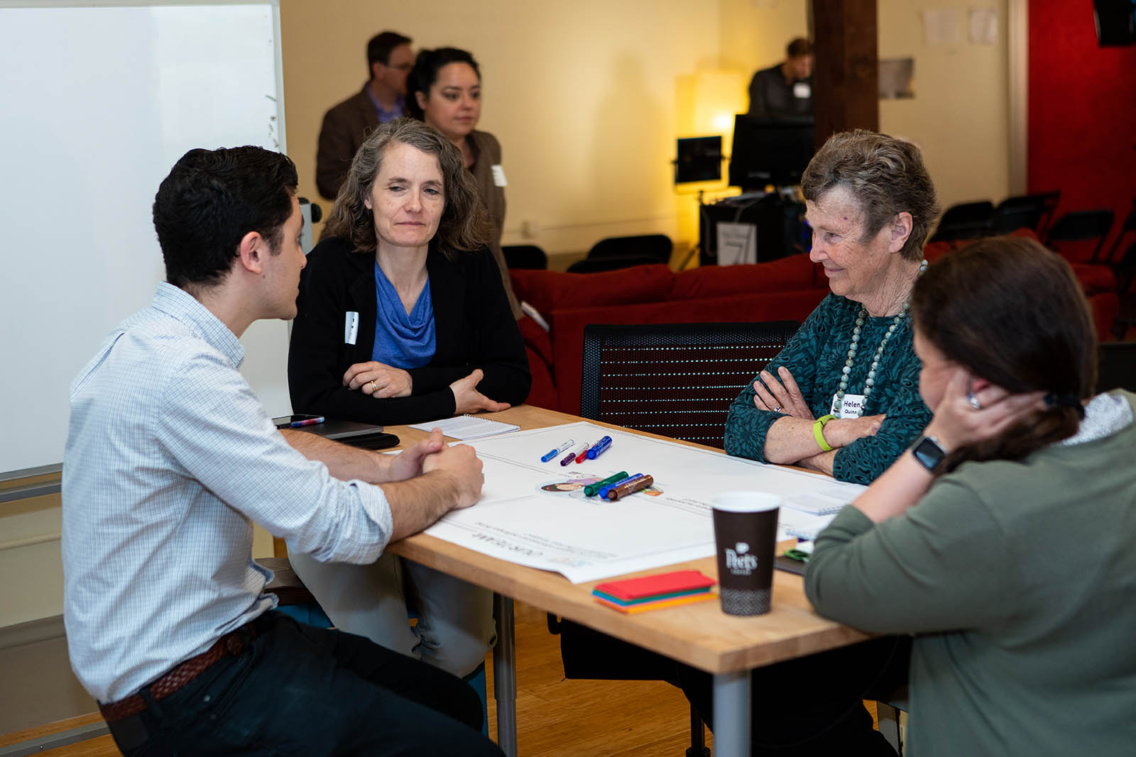Collaborating across disciplines. Concord Consortium developer Eli Kosminsky and Director of Impact Jen Goree brainstorm with learning researcher and assessment specialist Britte Cheng and Helen Quinn, Professor Emerita of Particle Physics and Astrophysics.